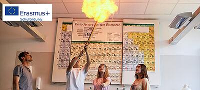 Schülerinnen und Schüler führen in Chemiesaal ein Experiment mit einer Stichflamme durch