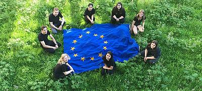Schülerinnen und Schüler sitzen um eine EU-Flagge herum auf grünem Rasen