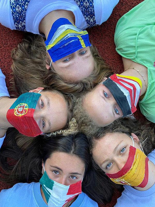 5 Mädchen mit Papiermasken, die Länderfahnen zeigen. Von oben fotografiert.