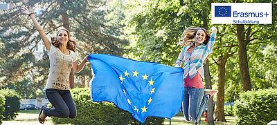 Zwei junge Frauen springen mit einer Europafahne in die Luft