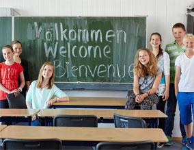 Schülerinnen und Schüler vor Schultafel